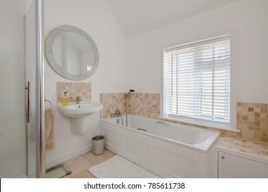Bright white home restroom with wall handwash basin compact bath and shower, large circular mirror venetian window blind and tiled splashback