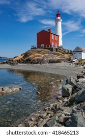 Bright white lighthouse and red tender building with rock and beach foreground