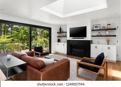 Bright and White Living Room with Fireplace in New Home. Features Large Skylights and Sliding Glass Doors with Exterior View of Deck and Trees