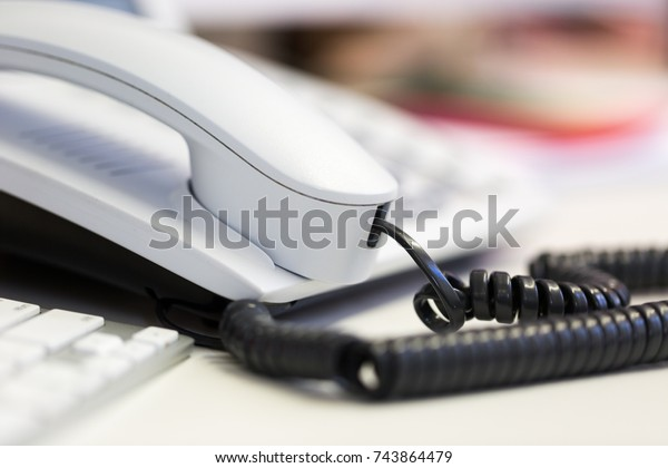 Bright white office telephone station on desk. Close up macro view, low angle perspective