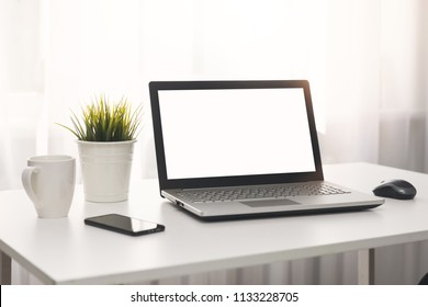 bright white workplace with laptop on the table in the room
