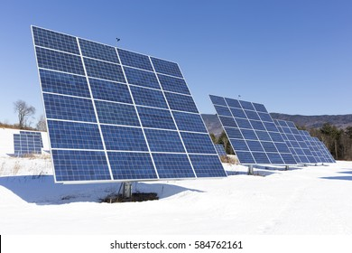 A bright winter sun shining on an array of solar panels in Vermont.