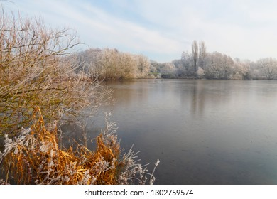 Bright winter sunshine starts to warm a frost covered landscape surrounding a frozen lake