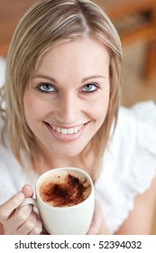 Bright woman drinking a coffee sitting on a sofa at home