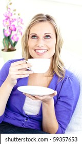 Bright woman enjoying her coffee sitting on the sofa in the living room