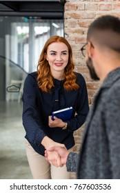 Bright woman meeting her interviewer at a job interview