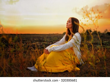 Bright woman relax sitting on a sunset autumn field