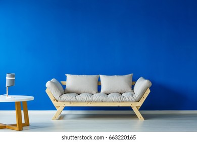 Bright wooden settee standing against a blue wall