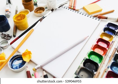 Bright workplace of creative artist mockup. Blank sketchbook surrounded by variety of drawing supplies. Art, workshop, painting, drawing, inspiration, craft, creativity concept