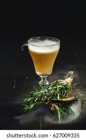 Bright yellow alcohol cocktail garnished with rosemary and cinnamon set on fire on black background