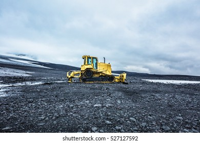 Bright yellow bulldozer on a gray plateau. Summer in 2016 Iceland