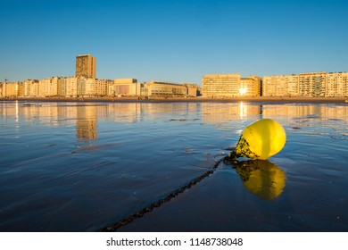 Bright yellow buoy on the beach of Oostende with city skyline in the background.
