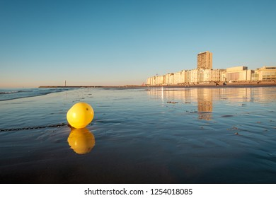 Bright yellow buoy on the beach of Oostende with city skyline in the background