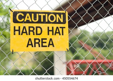 Bright yellow caution hard hat area sign on a chain link fence with a newly constructed bridge and crane in the background.