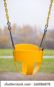 Bright yellow chain swing with protection belt on kids playground