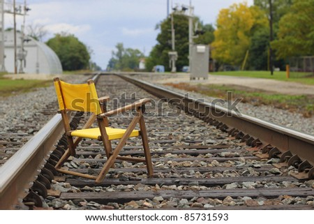 bright yellow chair tempts fate on a train track