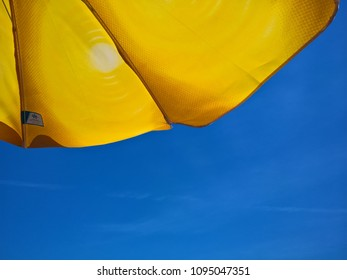 Bright yellow color umbrella near sea under blue sky on the beach. close-up photo of sky and yellow umbrella on holiday.