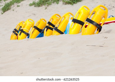 Bright yellow and colorful life saving equipment on the beach sand