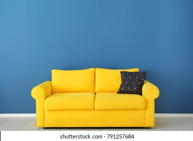 Bright yellow couch near color wall