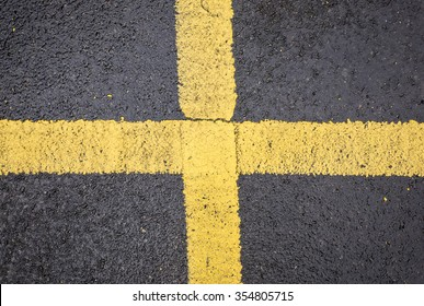 Bright yellow cross on road floor
