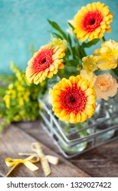Bright yellow daisies in little bottles in front of blue background