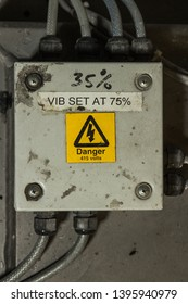 Bright yellow danger high voltage 415 volts on electrical equipment with four bolts on holding a panel onto the wall with thick heavy duty wires cables coming out in industry factory.