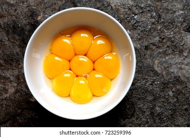 Bright yellow egg yolks in a white bowl with stone floor as background