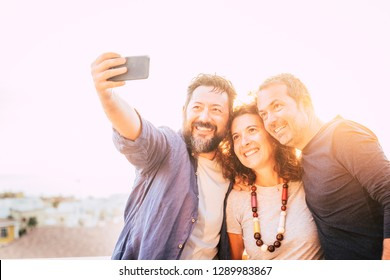 Bright yellow filter group of caucasian 40 years old people men and woman taking selfie picture with smart phone device - backlight and white sky in bnackground - happy leisure activity toncept