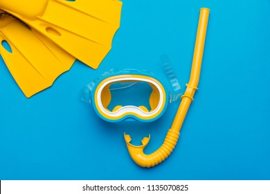 Bright yellow flippers and diving mask on a vibrant backround