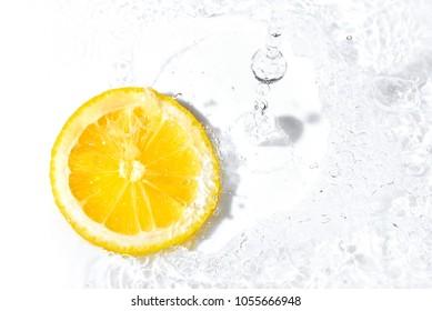 Bright yellow fresh lemon slice and water splash. Tasty and healthy food