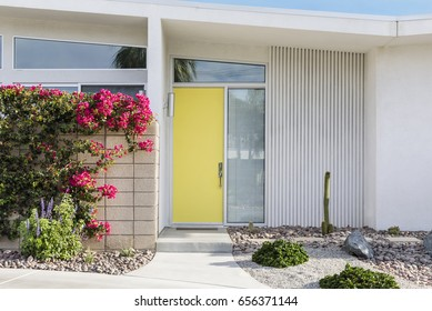 Bright yellow front door of a modern house