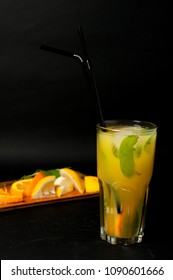 bright yellow glass with lemonade summer cocktail with lemon, mint, orange on a black background with chopped slices