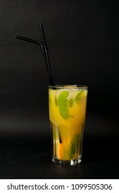 bright yellow glass with lemonade summer cocktail with lemon, mint, orange on a black background