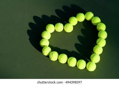 Bright yellow green tennis balls in heart shape love on dark green court background