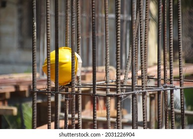 Bright yellow helmet left by the workers at a construction site with shallow depth of field. Thousands of migrant laborers have fled metropolitan cities due to Covid-19, Corona virus.