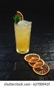 Bright yellow lemonade cocktail with orange and lemon on black background