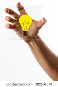 Bright yellow light bulb icon on piece of square shaped glass held in a single hand over isolated white background