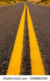 Bright yellow lines, indicating a no-passing area, disappears into the distance around a curve while separating the driving lanes on a country road on San Juan Island.