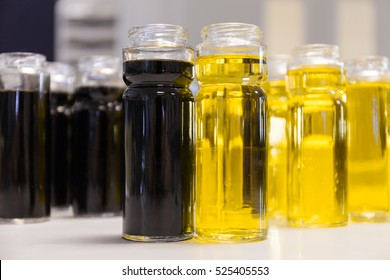 Bright yellow olive oil and black balsamic vinegar on the restaurant kitchen table. A lot of bottles with two foreground. Bottling of dressing.