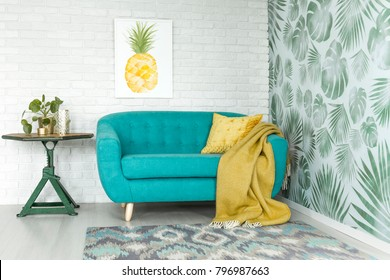 Bright yellow pineapple painting hanging over a stylish turquoise sofa with yellow blanket and pillow in a scandi style apartment interior