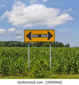 Bright yellow road sign in corn field with two arrows New Years concept with arrows pointing away from old year 2014 to new year 2015 with blue sky and cumulus clouds. Concept goodbye 2014 hello 2015