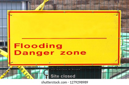 Bright yellow sign warning of flooding in public space with room for copy or text