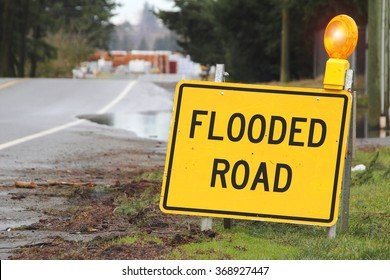 A bright yellow sign warns motorists that the road is flooded/Outdoor Sign Stating Flooded Road/A bright yellow sign warns motorists that the road is flooded.
