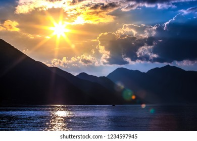 The bright yellow sun beams behind the clouds, above the silhouettes of picturesque and attractive mountains in the blue water of the Adriatic Sea gulf. Sunset on Boka Kotorska Bay, Kotor, Montenegro.