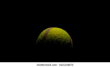 Bright Yellow Tennis Ball with dramatic shadows on a black background