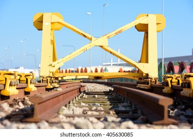 Bright yellow train buffer stop or bumper at the end of a railway track.