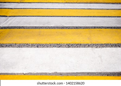 Bright yellow and white stripes of zebra crossing. Striped pedestrian crosswalk.