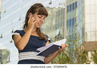 Bright young business woman on a background of office building. Young European / Caucasian female model. Woman with phone.