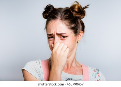 Bright young woman covers his nose due to bad smell, dressed in a pink overalls, isolated on white background