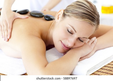 Bright young woman enjoying a back massage with hot stone in a spa center